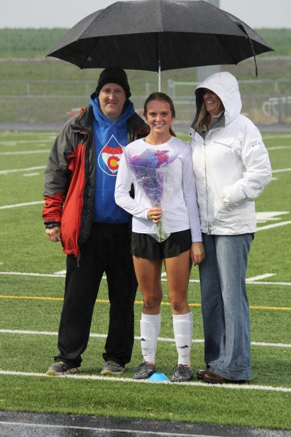 Kennidy Sakalosky stands with her parents after receiving flowers on senior night.