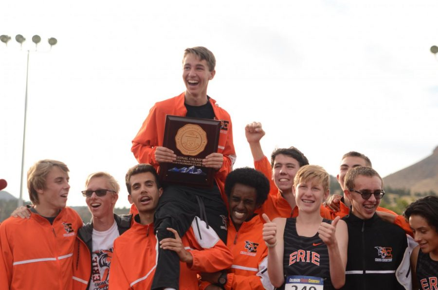 Luke Fritsche sits on his teammates' shoulders while holding Erie's championship plaque.