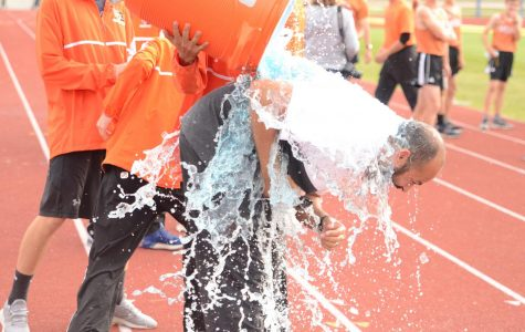 Erie's cross country team dumps Gatorade on their coach Brandon Harvard  after qualifying for state in Lyons at the Colorado 4A regional cross country meet.