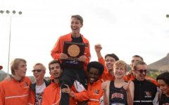 Luke Fritsche being held up by the cross country team with team's trophy after winning regionals